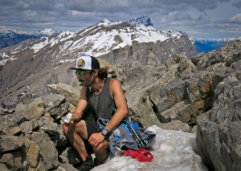 Eating a ProBar in the rock shelter (which offers mininal shelter) on top of Ha Ling Peak, 2408m, four hours and nine minutes after leaving downtown Canmore. Mighty Mount Temple is in the background at far left looking closer than it actually is.